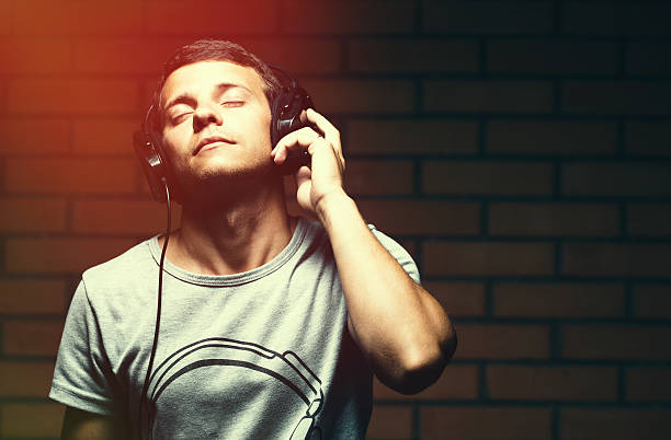 portrait of a handsome young man listening to music - dance music stock pictures, royalty-free photos & images