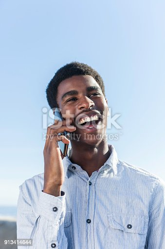 492529287istockphoto Portrait of a handsome young man talking on his mobile phone and laughing. 913414644