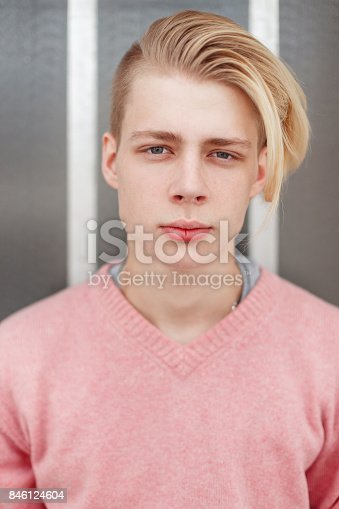 846124694 istock photo Portrait of a handsome young man with a blond hairstyle in a pink sweater near the wall 846124604