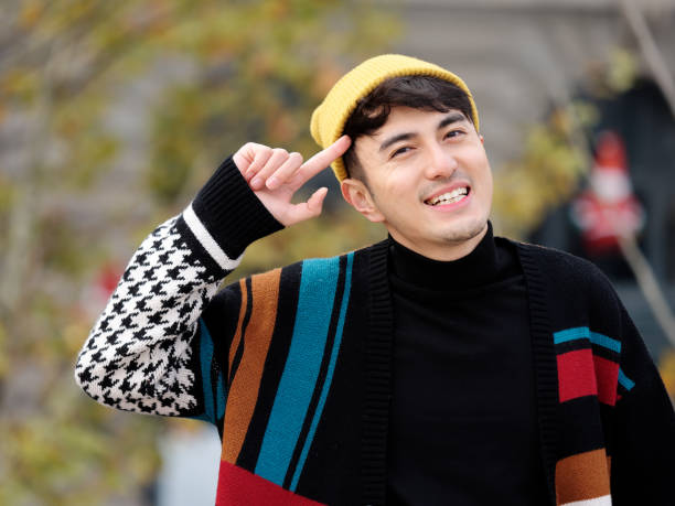 Portrait of a handsome young man with colorful woolen sweater and yellow hat looking at camera and smiling with finger point to his head, winter fashion, cool young man lifestyle. stock photo