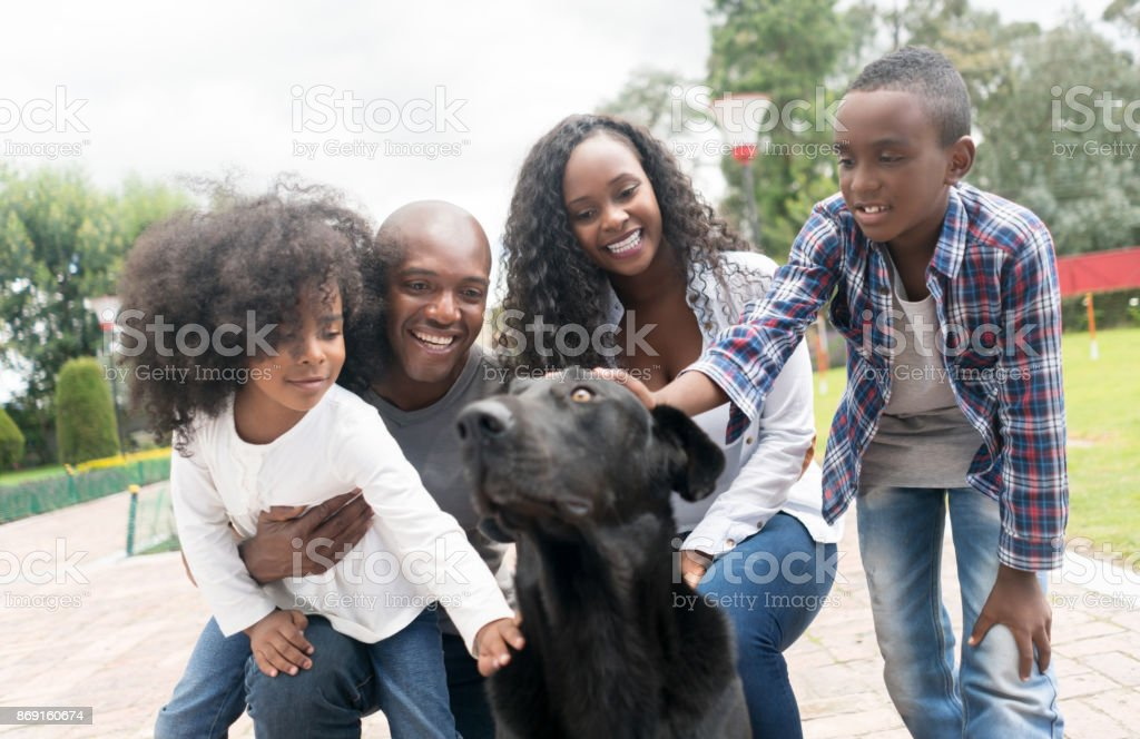Portrait of a happy African American family adopting a dog stock photo