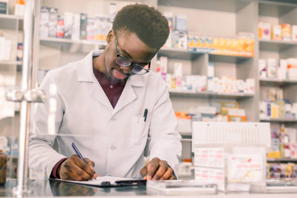 Portrait of a happy African American pharmacist writing prescription at workplace in modern pharmacy Portrait of a happy African American pharmacist writing prescription at workplace in modern pharmacy. technician stock pictures, royalty-free photos & images