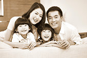 portrait of a happy asian family sitting on couch at home looking at camera smiling, black and white.