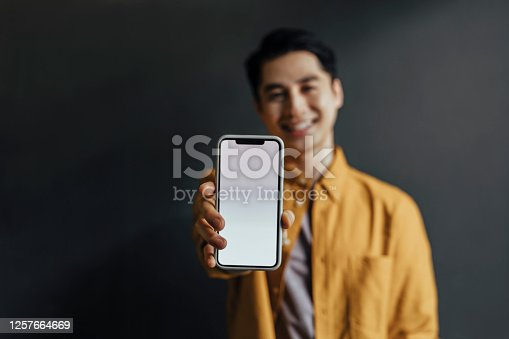 Smiling man standing against a gray background and using his smartphone.