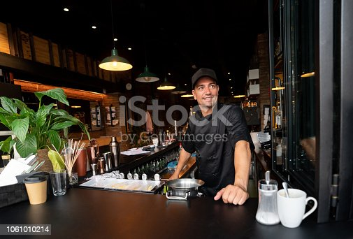 Portrait of a happy barista working at a cafe and looking at the camera smiling – food and drink concepts