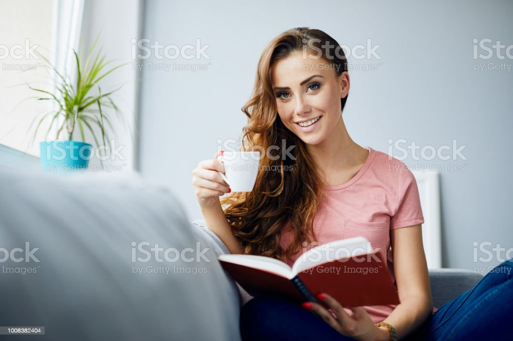 Portrait Of A Happy Beautiful Young Woman Holding Book And