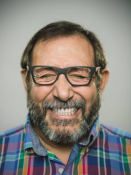 Portrait of a happy caucasian man with glasses and beard. Portrait of a real spanish man with big smile. Studio photography with sharp focus on eyes. The man wears modern glases and shirt and has a denture. cheesy grin stock pictures, royalty-free photos & images
