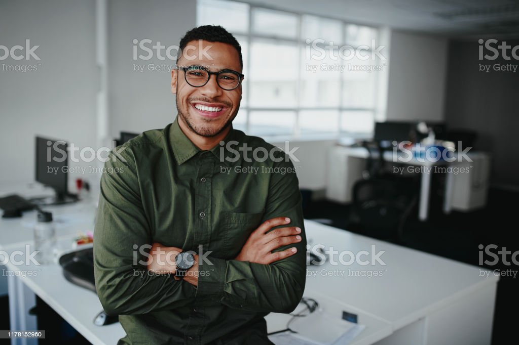 Portrait of a happy confident young african american businessman standing with his arms crossed looking at camera Portrait of young and successful businessman in modern office Adult Stock Photo