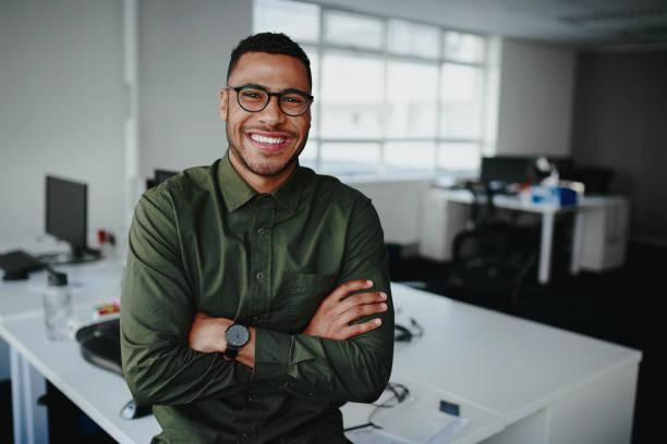 一個快樂自信的年輕非洲裔美國商人站在他的手臂交叉看著相機的肖像 - 年輕成年人 個照片及圖片檔
