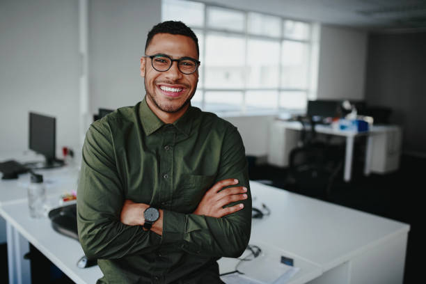 Portrait of a happy confident young african american businessman standing with his arms crossed looking at camera Portrait of young and successful businessman in modern office young adult stock pictures, royalty-free photos & images