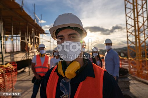 Portrait of a happy construction worker at a building site wearing a facemas with a group of workers at the background