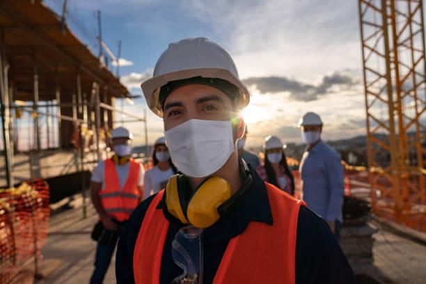 portret szczęśliwego pracownika budowlanego na placu budowy - kask ochronny odzież ochronna zdjęcia i obrazy z banku zdjęć