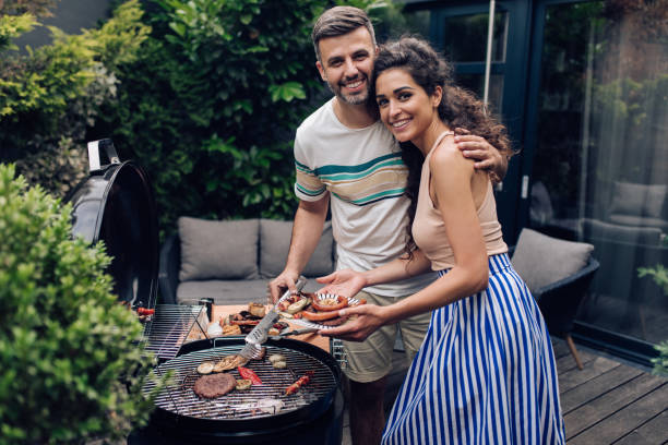 Portrait of a happy couple making barbecue stock photo