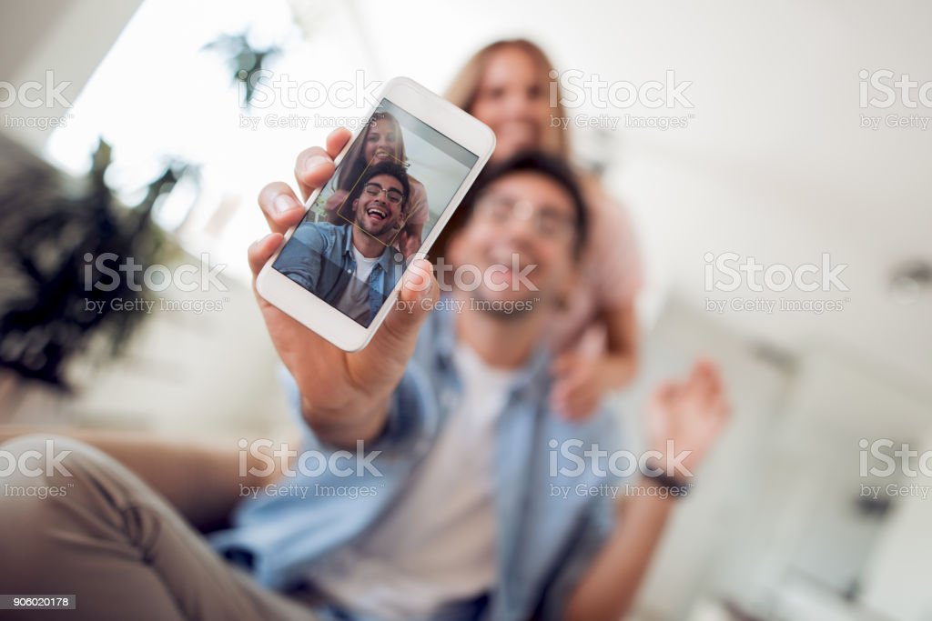 Portrait of a happy couple making selfie photo with smart phone stock photo