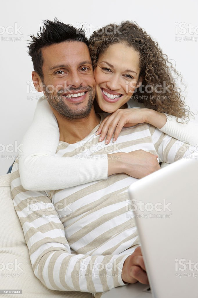 Portrait of a happy couple with laptop on sofa royalty-free stock photo