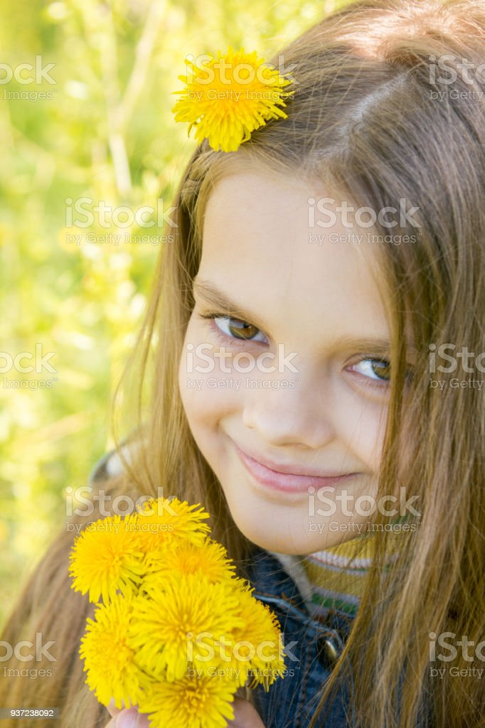 Portrait of a happy eight year old girl with dandelions in hands, against a background of green foliage stock photo