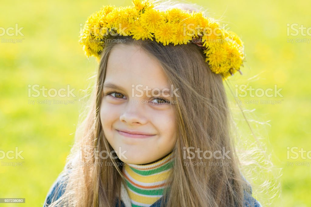 Portrait of a happy eight-year-old girl with a wreath of dandelions on her head, against the background of a spring clearing stock photo
