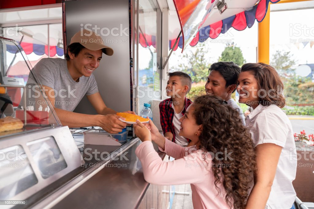 Portrait of a happy family buying food at an amusement park - lifestyle concepts - Stock image .