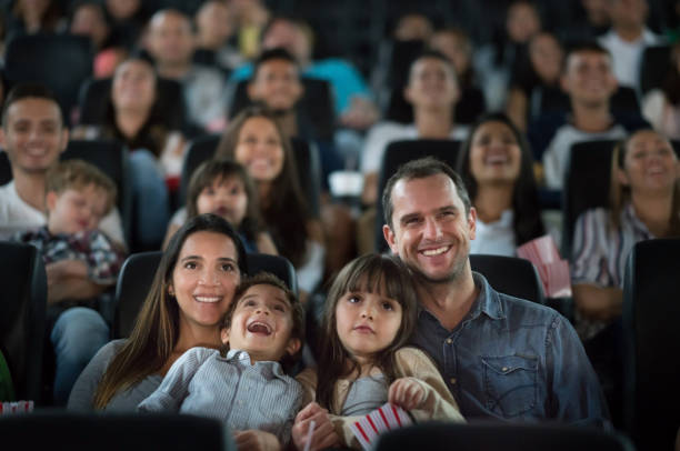 portrait of a happy family having fun at the cinema - movie theater stock photos and pictures