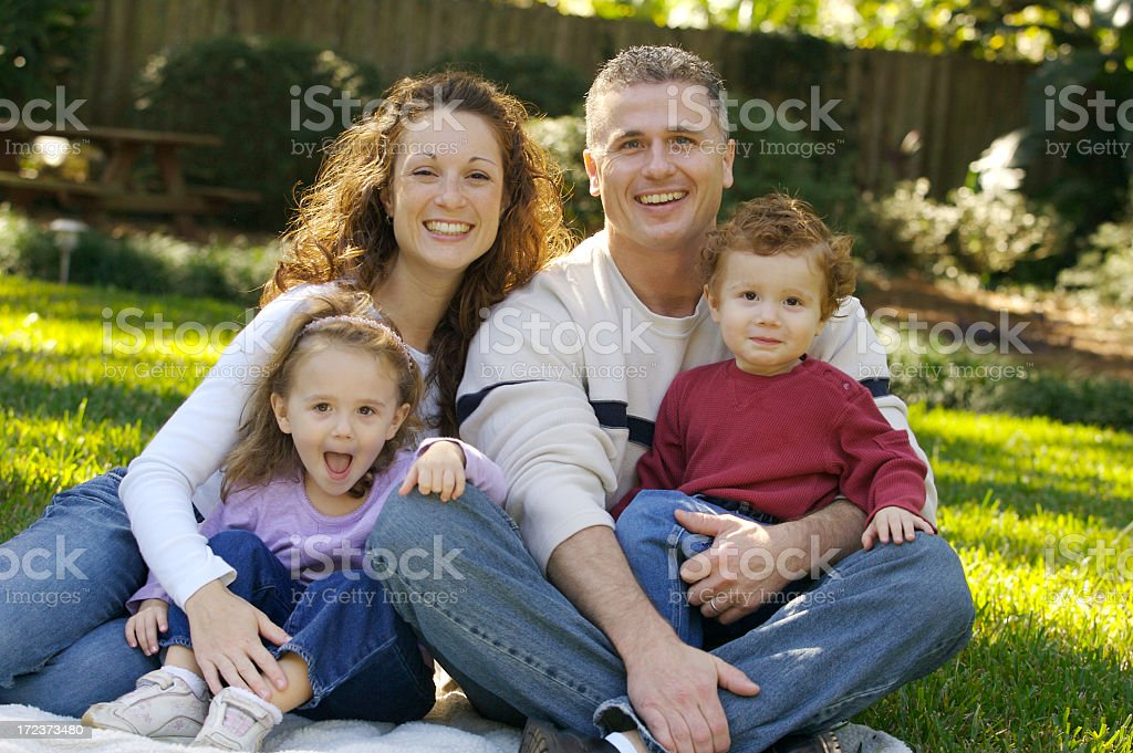 Portrait of a happy family sitting on their garden stock photo