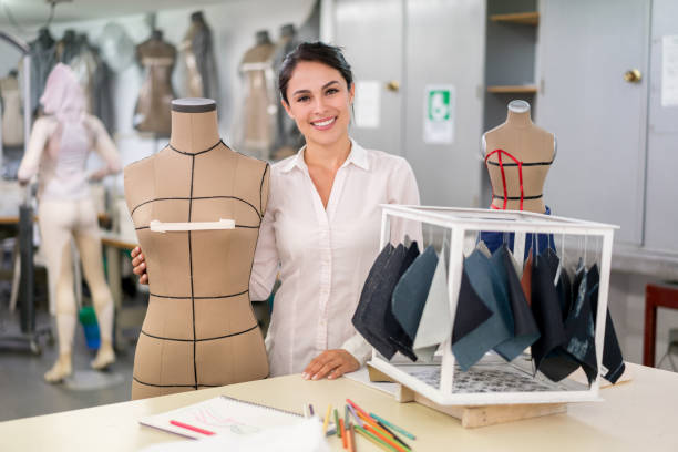 Portrait of a happy fashion designer at her atelier Portrait of a happy fashion designer at her atelier looking at the camera smiling designer baby stock pictures, royalty-free photos & images