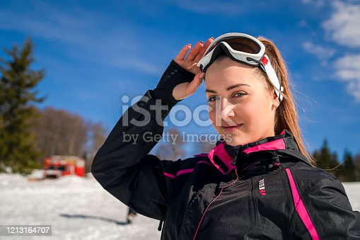 Portrait of a happy female skier smiling outdoors and looking at the camera wearing goggles - winter sports concepts