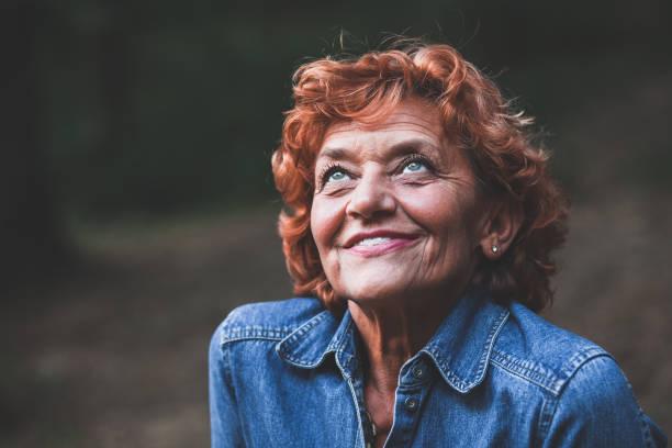 porträt einer glücklich fünfzig jahre alte frau, im freien - altes damenhaar stock-fotos und bilder