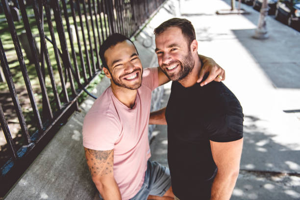 Ein Porträt eines glücklichen schwulen Paares im Freien im urbanen Hintergrund – Foto