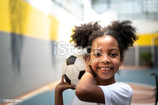 Portrait of a happy girl holding a soccer ball during physical activity class