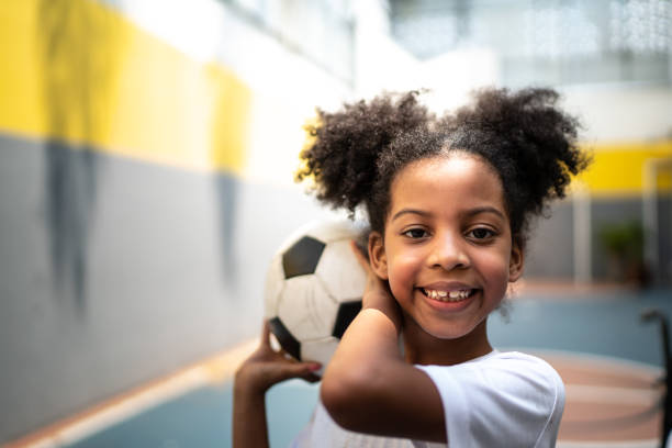 Portrait of a happy girl holding a soccer ball during physical activity class stock photo