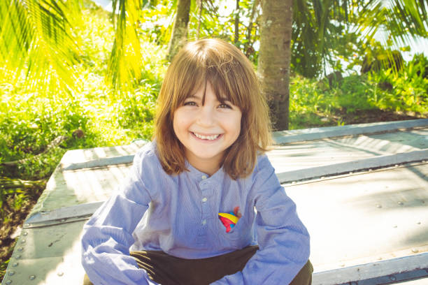 Portrait of a happy kid smiling at the camera in a tropical location stock photo