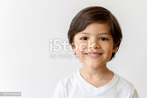 Portrait of a happy Latin American boy looking at the camera smiling over a white background