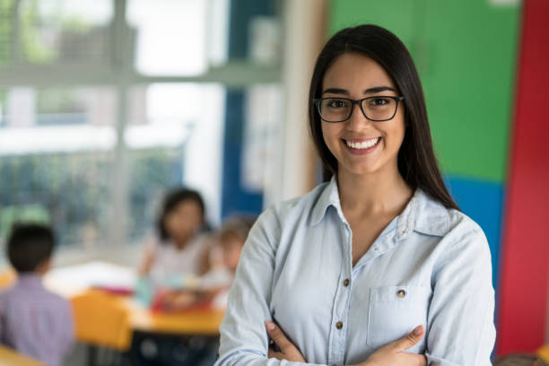 Portrait of a happy Latin American teacher at the school Portrait of a happy Latin American teacher at the school looking at the camera smiling - education concepts elementary age stock pictures, royalty-free photos & images