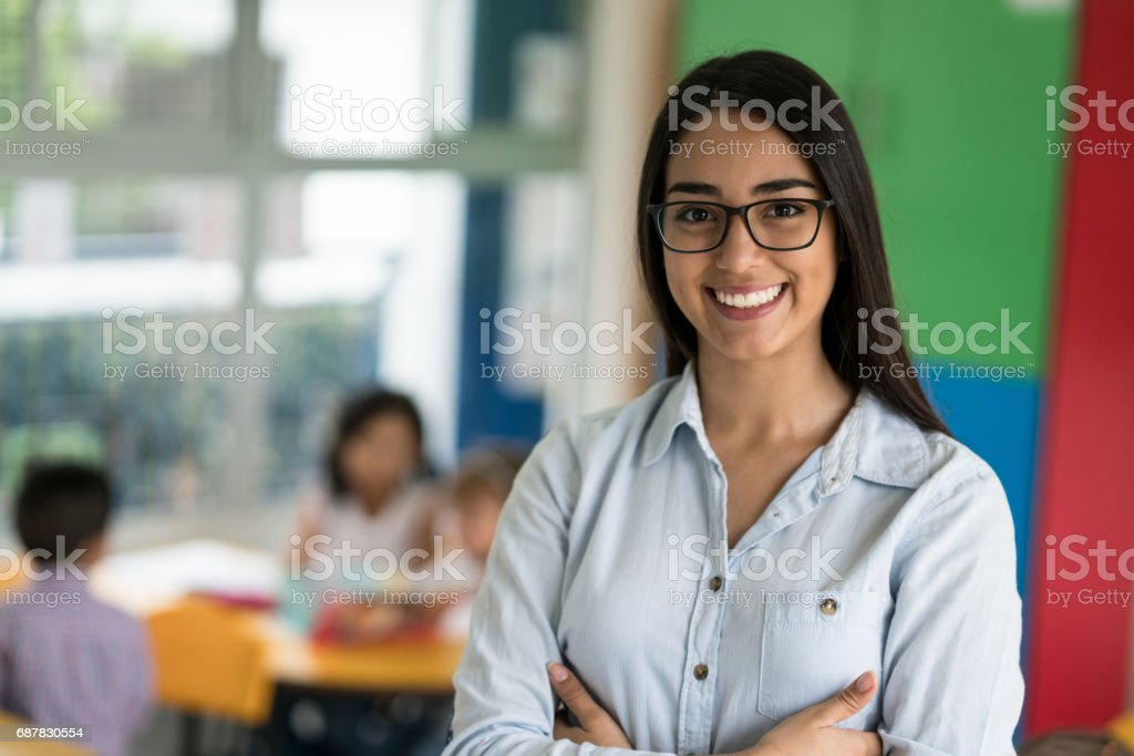 Portrait of a happy Latin American teacher at the school stock photo