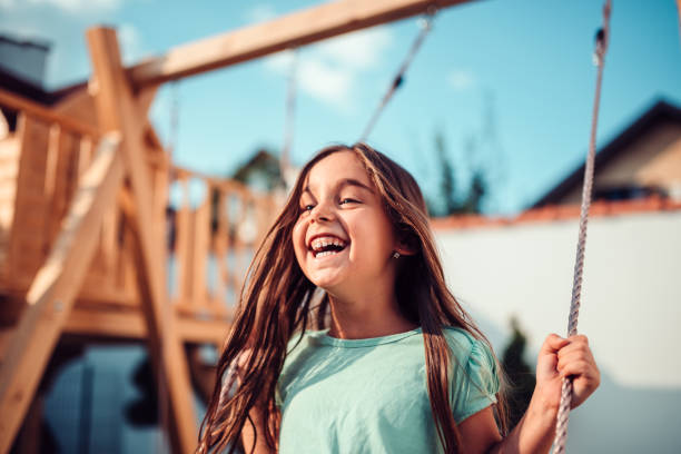 Portrait of a happy little girl sitting on a swing and smiling stock photo