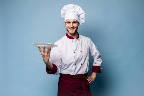 Porträt eines glücklichen männlichen Koch Koch stehen mit Teller isoliert auf hellblauem Hintergrund. – Foto