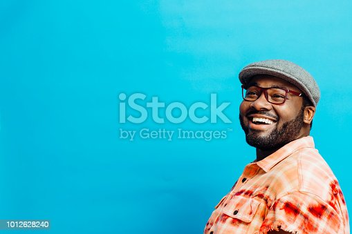 Portrait of a happy man in orange shirt looking up, with blue copy space around him