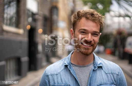 istock Portrait of a happy man smiling on the street 1187252487