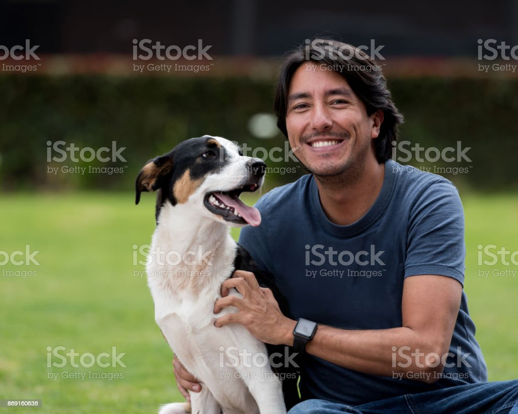 Portrait of a happy man with a mixed-race dog outdoors stock photo