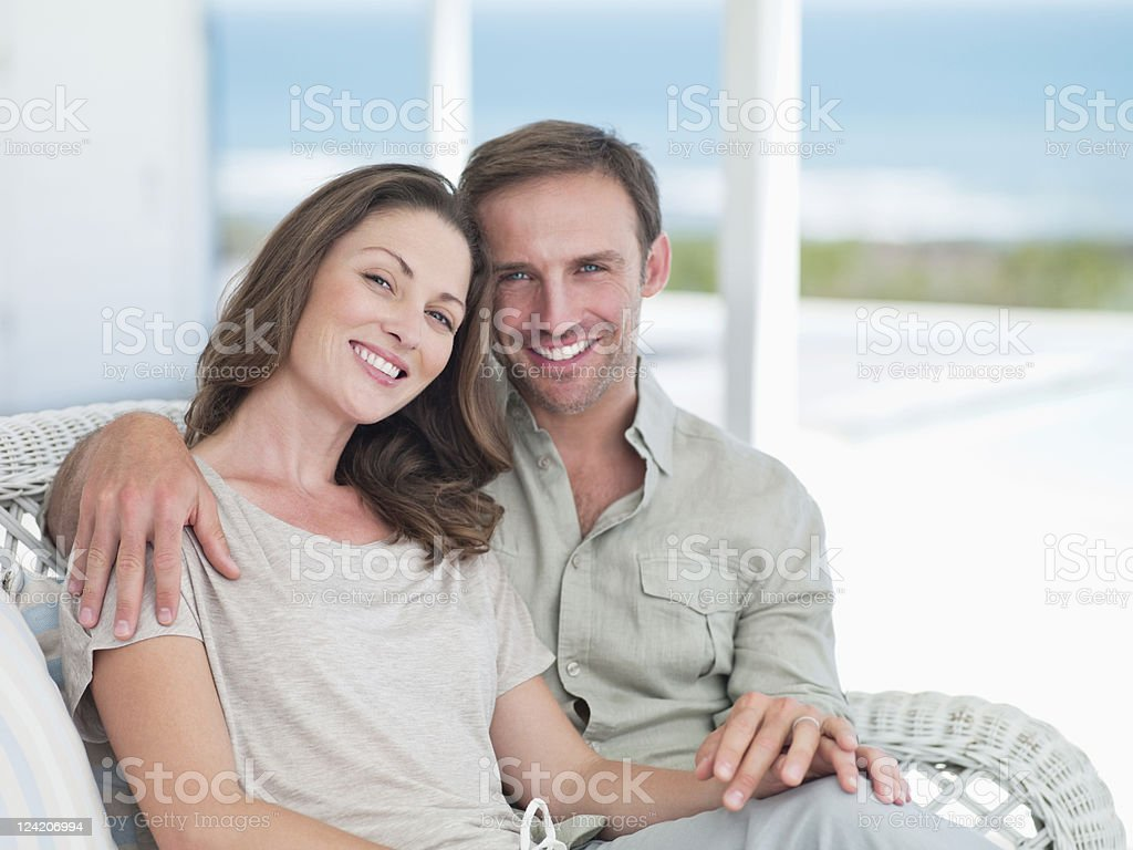 Portrait of a happy mid adult couple sitting on porch royalty-free stock photo