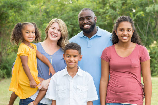 portrait of a happy mixed race family smiling - mixed race person stock pictures, royalty-free photos & images