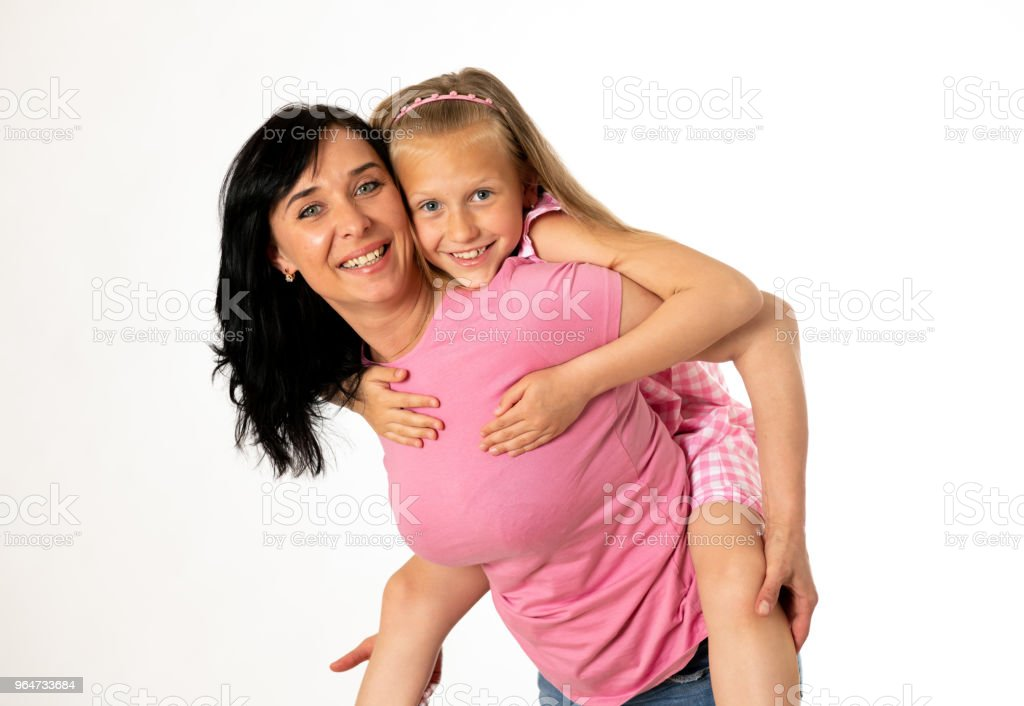Portrait of a happy mother and cute blonde little girl hugging and looking cheerful at the camera in studio on white background. Happy family and good and positive parent and child relationship royalty-free stock photo