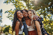 Cheerful excited positive modern group of female friends hugging together in park and laughing and having fun