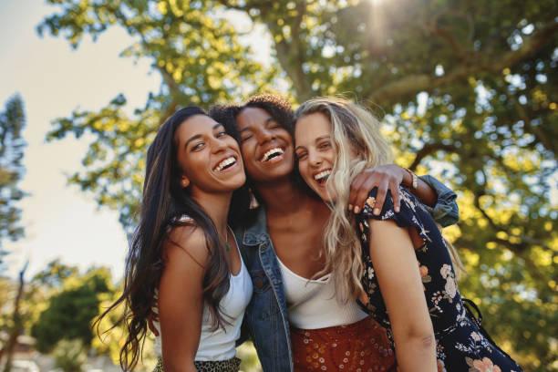 retrato de un grupo multiétnico feliz de amigas femeninas sonrientes - mujeres riendo y divirtiéndose en el parque en un día soleado - amistad fotografías e imágenes de stock