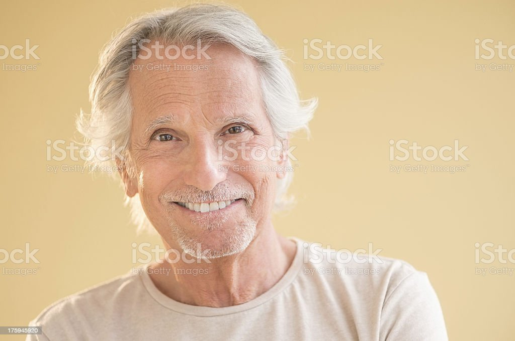 Portrait of a happy older gentleman on a tan backdrop royalty-free stock photo