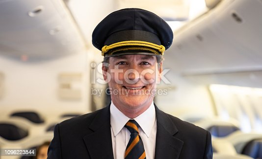 Portrait of a handsome male pilot in an airplane and looking at the camera smiling - travel concepts