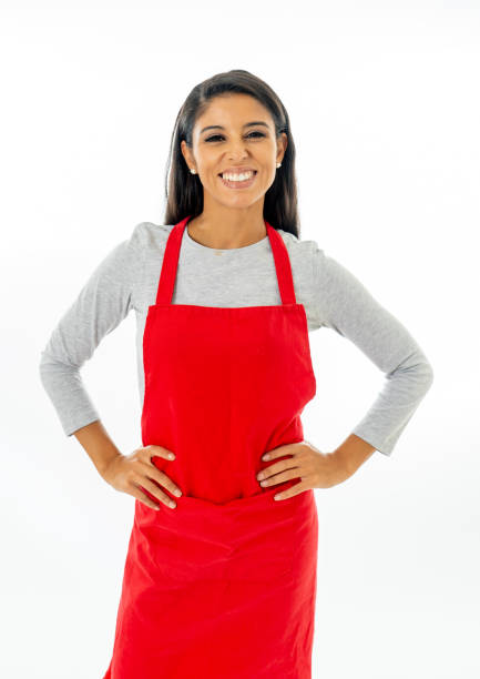 Portrait of a happy proud beautiful latin woman wearing a red apron learning to cook making thumb up gesture in cooking classes small business and homemade spanish food concept isolated on white Portrait of a happy proud beautiful latin woman wearing a red apron learning to cook making thumb up gesture in cooking classes small business and homemade spanish food concept isolated on white apron stock pictures, royalty-free photos & images