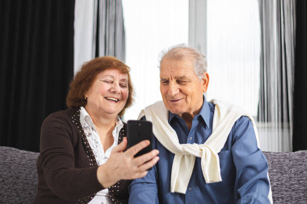 Portrait of a happy senior couple with a smartphone in hand. Senior couple make a video call or talk with someone dear stock photo