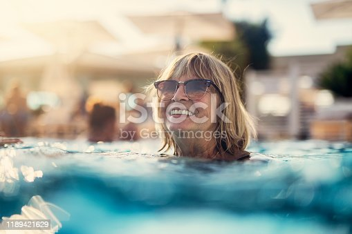Happy senior woman enjoying summer vacations. The woman is swimming in the pool. Nikon D850