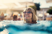 Happy senior woman enjoying summer vacations. The woman is swimming in the pool.\nNikon D850